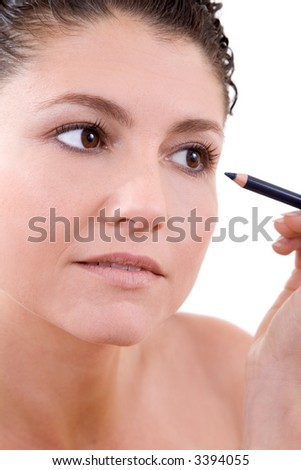 Beautiful brunette working on her makeup on white background