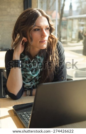 Beautiful brunette working on laptop in a city cafe - stock photo