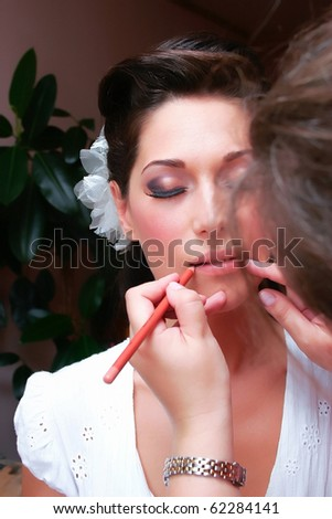 beautiful brunette young bride prepare for the event by makeup artist - stock photo