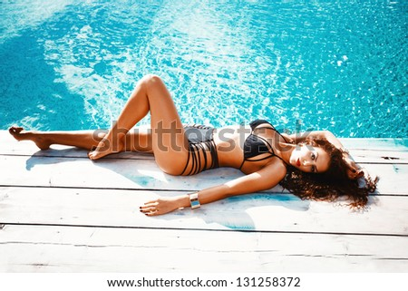 beautiful brunette young woman in bikini relax by pool summer day