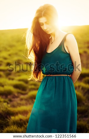 Beautiful brunette young woman in the green evenong meadow - stock photo
