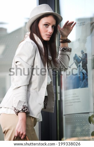 Beautiful brunette young woman outdoor with hat on looking at shop window display outside