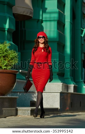 Beautiful brunette young woman wearing red dress, beret, gloves and walking on the street - stock photo
