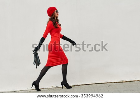 Beautiful brunette young woman wearing red dress, beret, gloves and walking on the street about the white wall