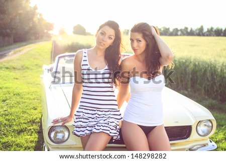 Beautiful brunettes in a dress and panties and corset posing beside the car, cabriolet, Pin Up style, fashion photography - stock photo