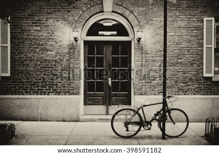 Beautiful building. Entrance door and bicycle, Manhattan New York. Classic apartment building in New York City. Vintage, retro picturesque postcard with sepia filter. - stock photo