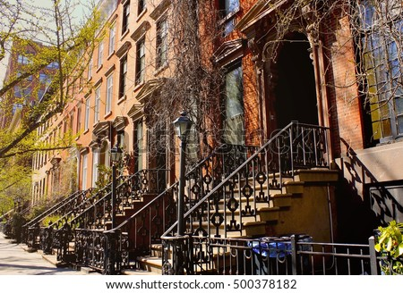 Beautiful buildings in Greenwich Village, Soho district. Urban landscape. Housing doors with stairs in Manhattan, New York city, USA. Typical luxury apartment buildings in NYC.