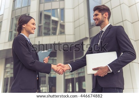 Beautiful business lady and handsome young businessman in classic suits are shaking hands and smiling, standing outside the office building