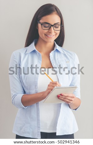 Beautiful business lady in smart casual wear and eyeglasses is writing in notepad and smiling, on a gray background