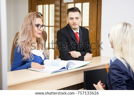 Beautiful business lady in the waiting area talking to the secretary abd giving her a folder with documents next to two employees who are waiting to talk to the secretary too