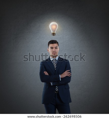 Beautiful business man with idea light bulb above head on gray background