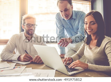 Beautiful business people are using a laptop, discussing affairs and smiling while working in office