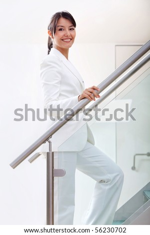 Beautiful business woman climbing stairs at the office - stock photo