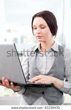 Beautiful business woman concentrating while working on computer at her office
