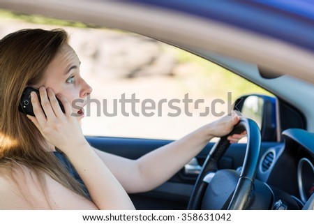 Beautiful business woman driving a car, talking on the mobile phone. Careful driving concept