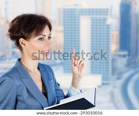 Beautiful business woman in an office with windows overlooking the luxurious new buildings, holds a meeting with colleagues, successful career of young people - stock photo