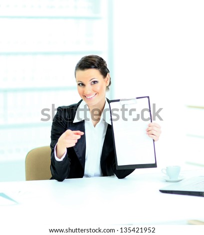 Beautiful business woman in the office, at the work place with the work plan.