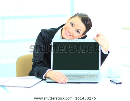 Beautiful business woman in the office, presentation of the laptop. - stock photo