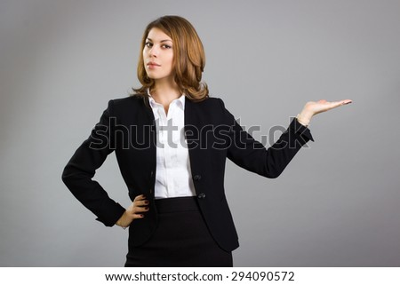 Beautiful business woman is pointing hand presenting something.