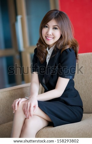 Beautiful business woman is sitting on sofa