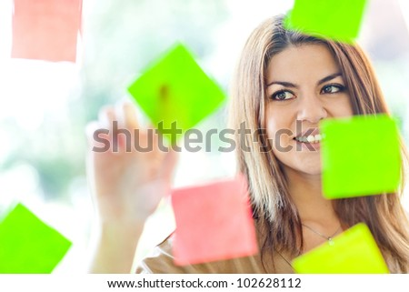 Beautiful business woman multitasking with lots of post-its - stock photo