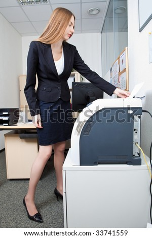 Beautiful business woman near to the printer - stock photo
