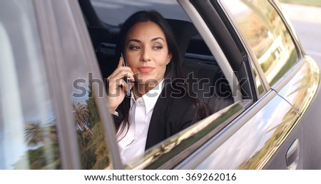 Beautiful business woman on phone in automobile - stock photo