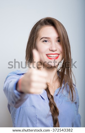 beautiful business woman showing thumbs up gesture, studio, isolated - stock photo