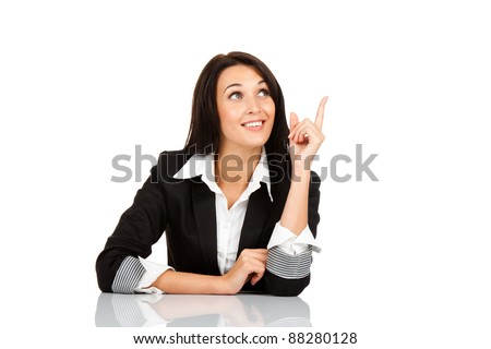 beautiful business woman sitting at the desk think looking up point finger to empty copy space, isolated over white background - stock photo