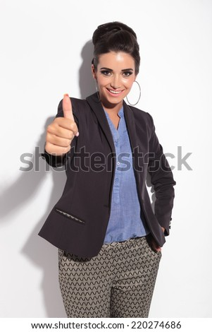 Beautiful business woman smiling while showing thumbs up, against a white wall - stock photo