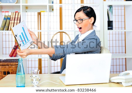 Beautiful business woman smiling while working with reports and statistics and using computer at her office