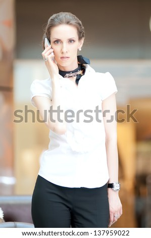 Beautiful business woman talking on cell phone over business background