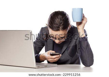 Beautiful business woman texting on the phone with a cup of coffee at her desk