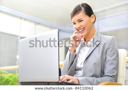 Beautiful business woman thinking about something while working no computer at her office - stock photo