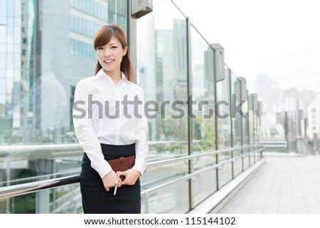 Beautiful business woman walking outside her office - stock photo
