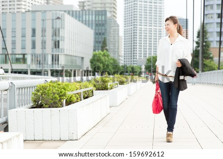 Beautiful business woman walking outside her office. Portrait of asian.  - stock photo