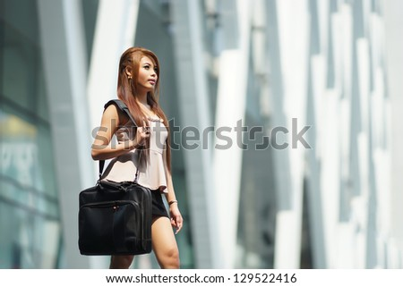 Beautiful business woman walking outside her office with briefcase.