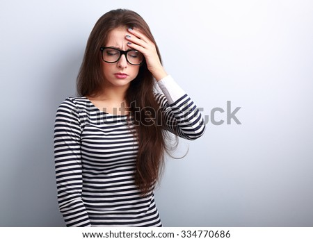 Beautiful business woman with headache holding head the hand with unhappy emotion on blue background - stock photo