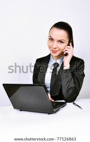 beautiful business woman with laptop talking by phone