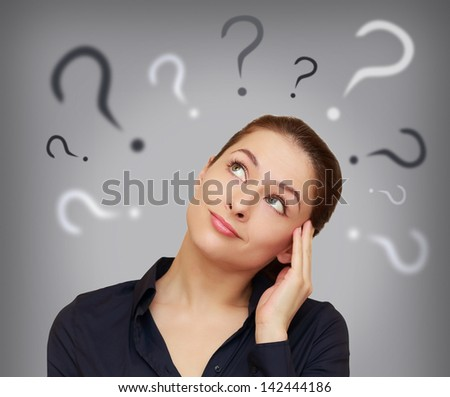 Beautiful business woman with question mark above the head looking up on grey background