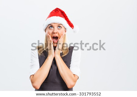 Beautiful business woman with Santa Hat is surprised because of something.Surprised business woman with Santa Hat