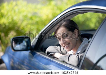 Beautiful businessw woman inside her car, smiling at camera