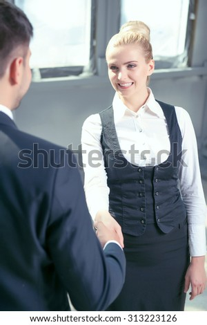 Beautiful businesswoman and her male colleague are shaking hands. They are looking at each other happily and smiling. The deal was done - stock photo