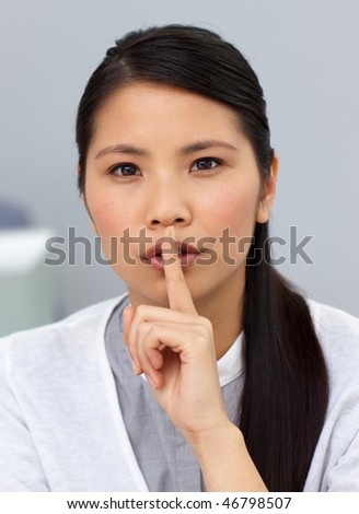 Beautiful businesswoman asking for silence in the office