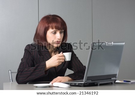 Beautiful businesswoman behind a desktop and a laptop with a coffee cup in a hand - stock photo
