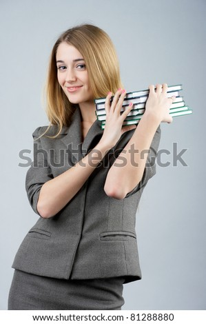 Beautiful businesswoman carrying stack of books - stock photo
