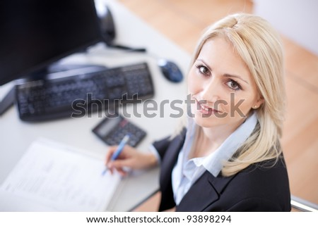 Beautiful businesswoman doing finances in the office - stock photo