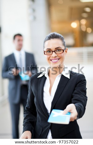 beautiful businesswoman handing over air ticket at airport - stock photo