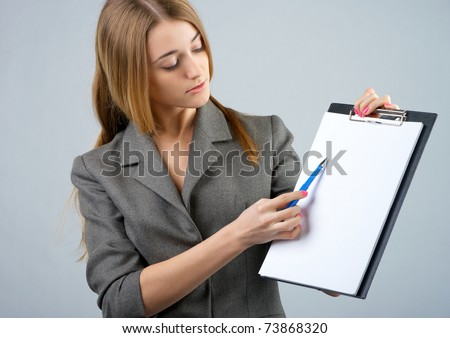 Beautiful businesswoman holding a clipboard and showing something - stock photo