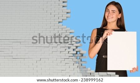 Beautiful businesswoman holding blank paper sheet. Dilapidated brick wall as backdrop. Business concept - stock photo